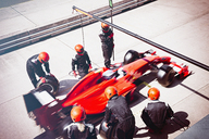 Pit crew replacing tires on formula one race car in pit lane - CAIF06483