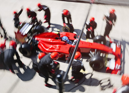 Overhead pit crew replacing tires on formula one race car in pit lane - CAIF06489