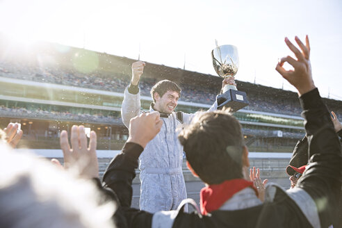 Formula one racing team cheering for driver with trophy, celebrating victory on sports track - CAIF06501
