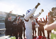 Formula one racing team and driver cheering, celebrating victory on sports track - CAIF06531