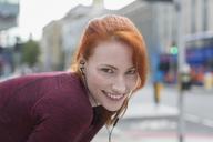 Portrait smiling female runner with headphones resting on urban sidewalk - CAIF06555