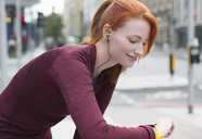 Smiling female runner with red hair and headphones checking smart watch - CAIF06558