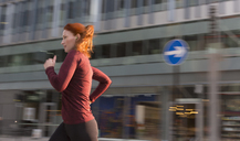 Female runner running along urban building - CAIF06561