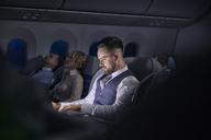 Businessman working on laptop on night airplane - CAIF06564