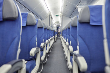 Empty blue seats in a row in airplane - CAIF06570