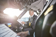 Male pilots with clipboard preparing in airplane cockpit - CAIF06573