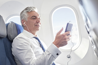 Businessman listening to music with headphones and mp3 player on airplane - CAIF06576