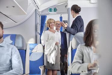 Flight attendant greeting passengers boarding airplane - CAIF06579
