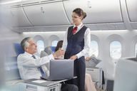 Flight attendant serving drink to businessman working at laptop on airplane - CAIF06585