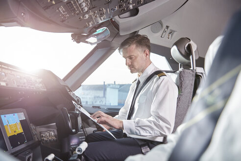 Male pilot with clipboard preparing in airplane cockpit - CAIF06588
