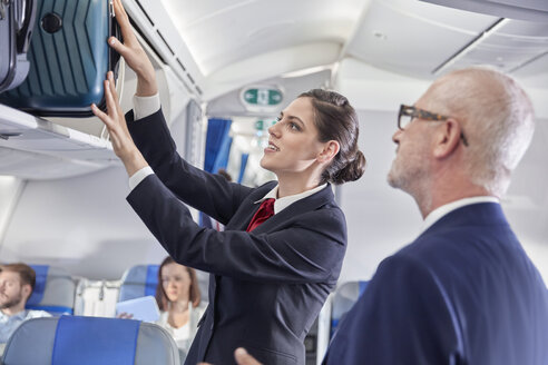 Flight attendant helping businessman place luggage in overhead compartment on airplane - CAIF06591