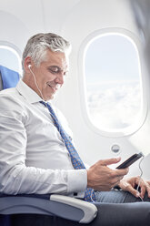 Businessman listening to music with headphones and mp3 player on airplane - CAIF06594