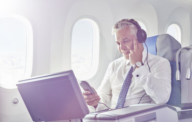 Businessman with headphones watching movie on airplane - CAIF06597