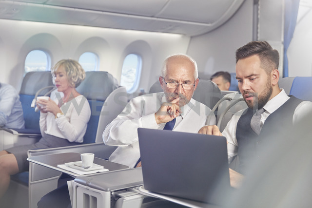 Businessmen working at laptop in first class on airplane - CAIF06600