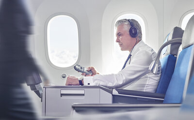 Businessman with headphones and remote control watching movie on airplane - CAIF06603