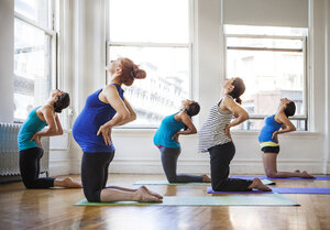 Pregnant women practicing yoga in gym - CAVF01126