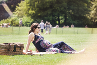 Pregnant woman sitting on grassy field in park - CAVF01132