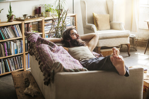 Thoughtful man relaxing on sofa at home - CAVF01144