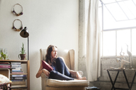 Thoughtful woman sitting on armchair at home - CAVF01153