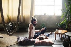 Man looking at woman lying on floor in living room - CAVF01162