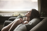 Woman looking away while relaxing on sofa - CAVF01171
