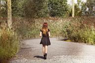 Rear view of woman walking on road by field - CAVF01216