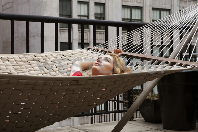 Thoughtful woman lying on hammock in patio - CAVF01252