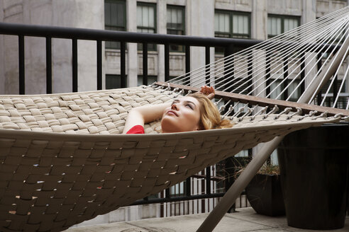 Thoughtful woman lying on hammock in patio - CAVF01252