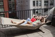 Cheerful friends lying on hammock in patio - CAVF01255
