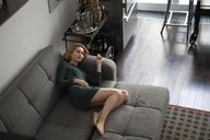 High angle view of woman lying on sofa at home - CAVF01258