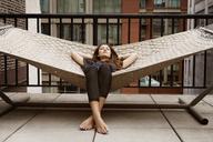 Woman sleeping on hammock in patio - CAVF01267