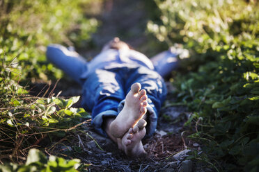 Man lying on field at farm - CAVF01294