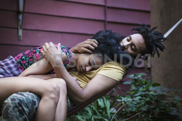 Couple relaxing on hammock in lawn - CAVF01312