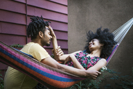 Woman playing with man's hair while lying on hammock in lawn - CAVF01315