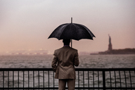 Rear view of man with umbrella standing by railing against sea - CAVF01336