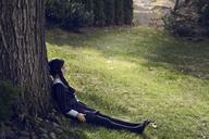 Girl sitting by tree trunk on field in lawn - CAVF01357