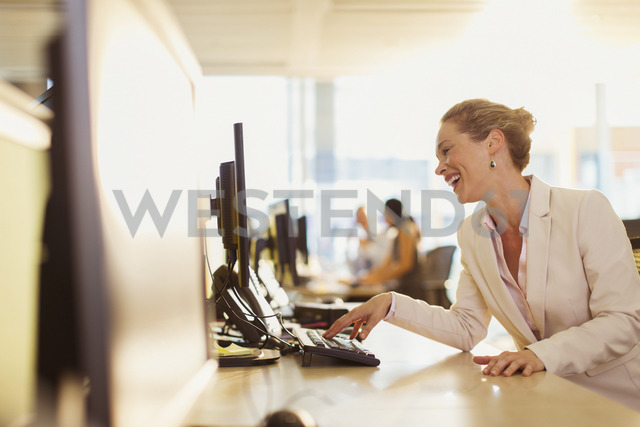 Laughing businesswoman working at computer in office - CAIF06606 - Paul Bradbury/Westend61