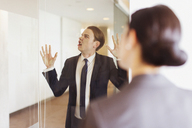 Silly businessman pressing face against office glass - CAIF06609