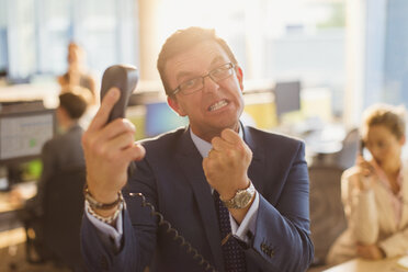 Furious businessman gesturing with fist at telephone in office - CAIF06612