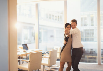 Businessman and businesswoman dancing in conference room - CAIF06615