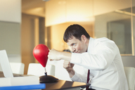 Businessman punching toy punching bag in office - CAIF06621