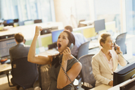 Exuberant woman on telephone celebrating good news in office - CAIF06624