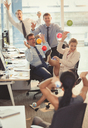 Playful business people throwing colorful plastic balls at each other in office - CAIF06627
