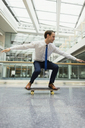 Playful businessman skateboarding in office corridor - CAIF06630