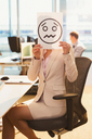 Portrait of businesswoman holding frowning face printout over her face in office - CAIF06633
