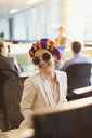 Portrait of smiling businesswoman in silly sunglasses and striped hat working in office - CAIF06639