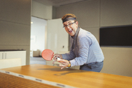 Portrait of enthusiastic businessman playing ping pong with tie wrapped around head in conference room - CAIF06642