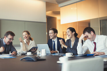 Business people laughing in conference room meeting - CAIF06645