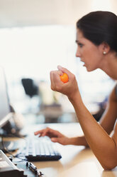 Businesswoman squeezing stress ball at computer in office - CAIF06648