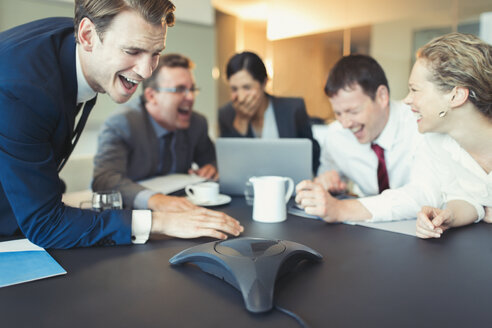 Laughing business people on conference call in conference room - CAIF06651